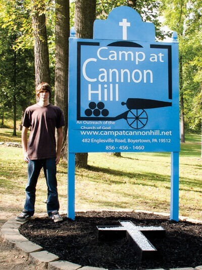 Ben Devan stands next to the new sign at Camp Cannon Hill.
