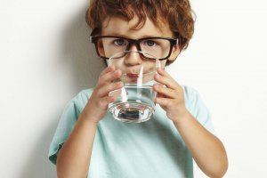 Portrait,Of,Boy,Drinking,Glass,Of,Water,Isolated,In,White
